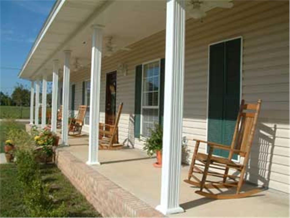 Front porch looking from right to left with multiple rocking chairs on porch