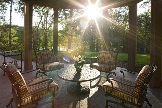Patio with four cushioned chairs areound a cirular table