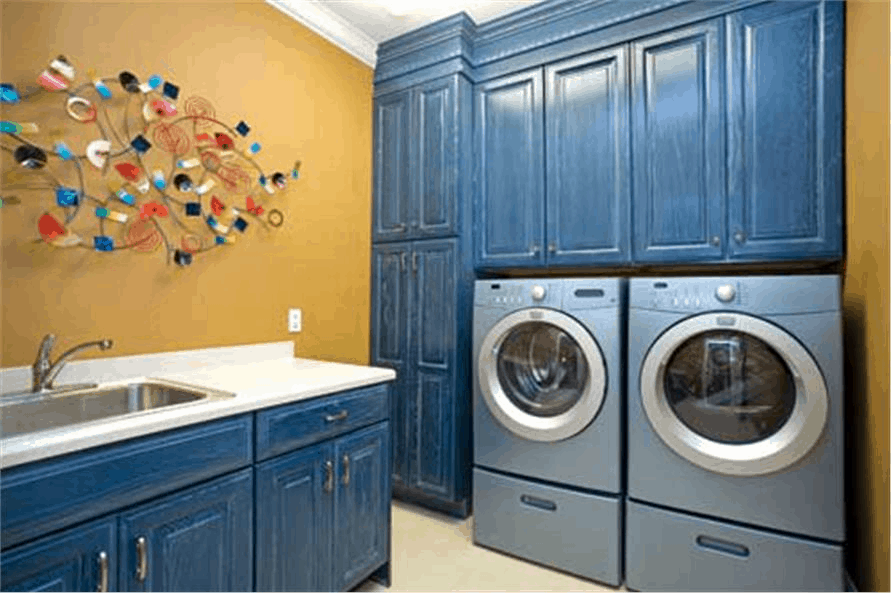 Laundry room with earth-tone color wall and blue pickled wood cabinets