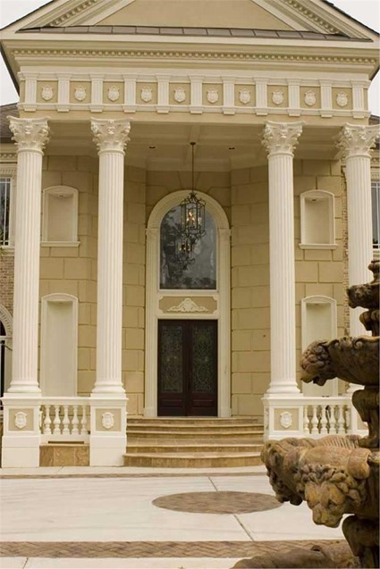 Front view of a European Manor style home that uses Corinthian support columns