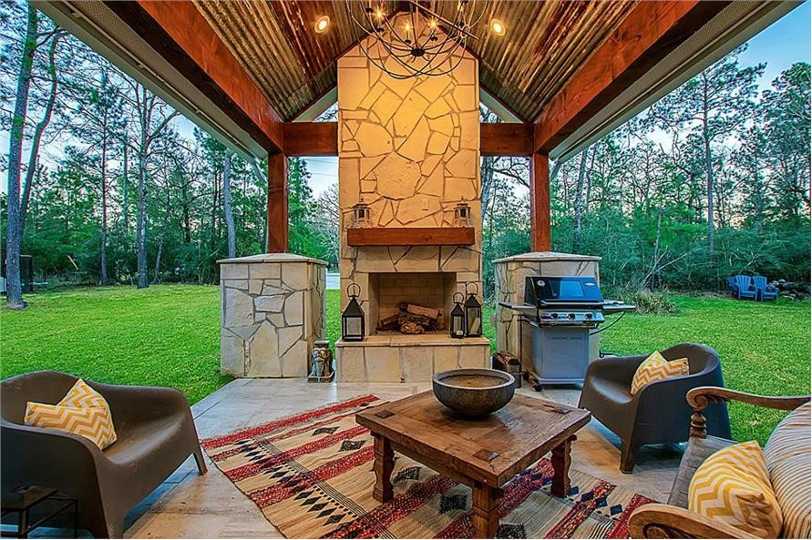 Sitting area in outdoor living space with fireplace and grilling area