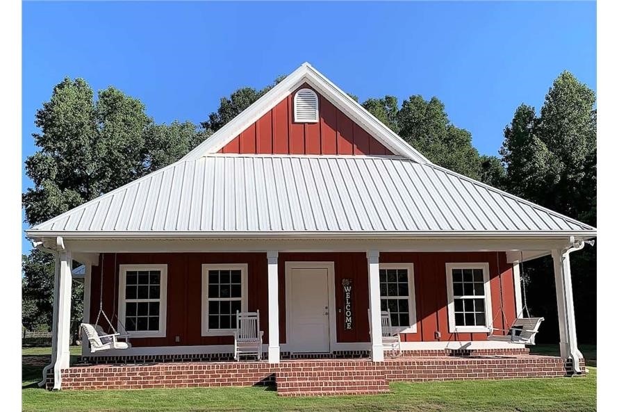 Bungalow style home with covered front porch and red board-and-batten siding