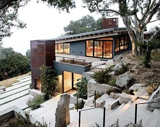 Home on a steep slope that uses a combination of trees, plants, and rocks to prevent erosion on the property