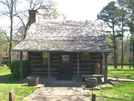 Typical log cabin with gable roof, porch that extends across the front of the home, and chimney