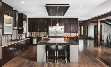 Kitchen with dark cabinets, drawers, and kitchen island countertop; stainless-steel appliances and light fixtures; and wood flooring