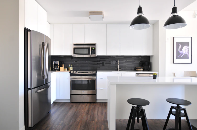 Minimalist white-gray-and black kitchen that is enhanced by the sleek white cabinets