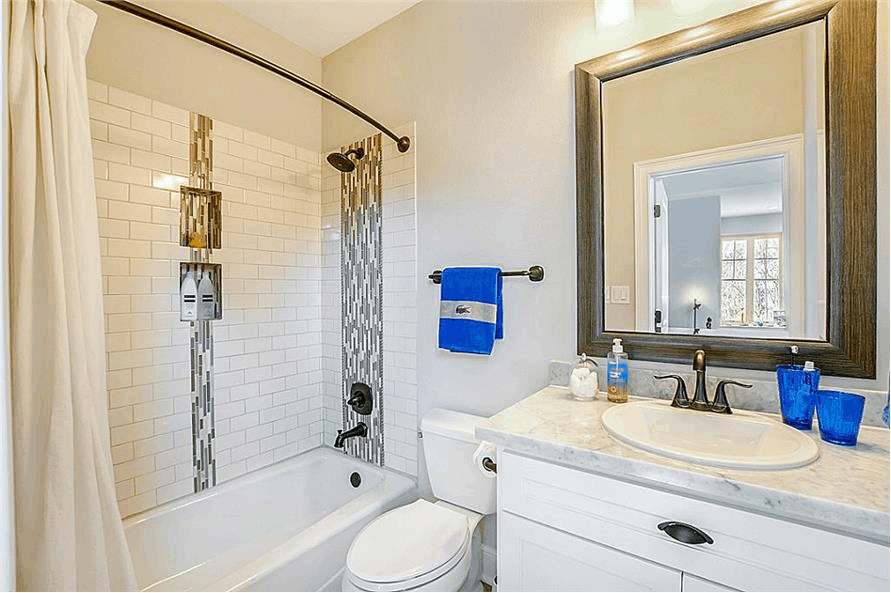 Bathroom tub surround covered in white subway tiles and tall gray-and-white tile accents