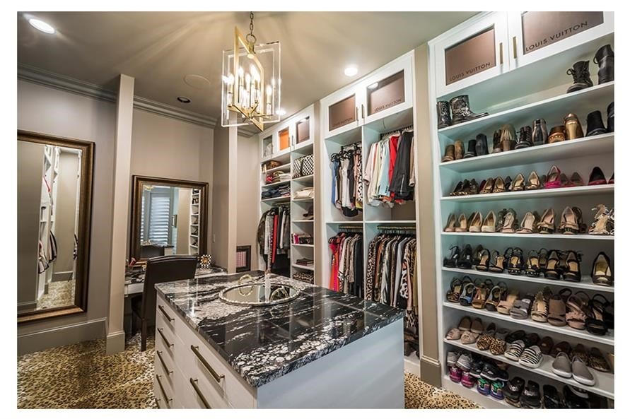 Large walk-in closet in a master suite showing shoe collection and overhead cabinets
