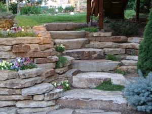 Retaining wall, stone steps, and low-maintenance plants and shrubs make for an interesting yard