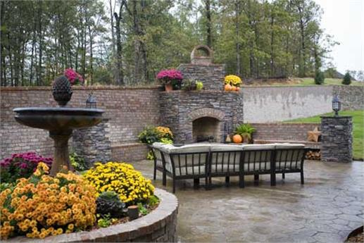 Rear patio with brick privacy wall, stone pavers, and stone outdoor fireplace