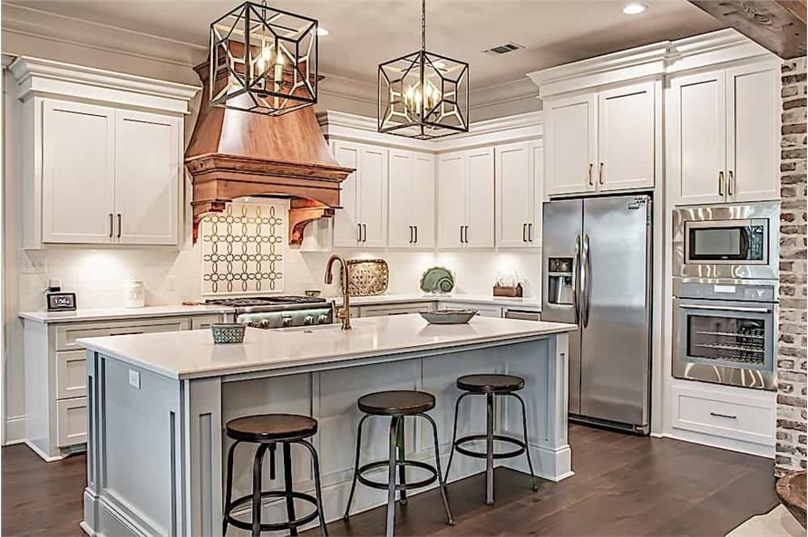White kitchen with large decorative vent hood and square pendent lights that make a statement