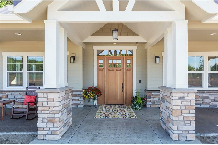 Front door of transitional Craftsman home with white timbers and stone column bases