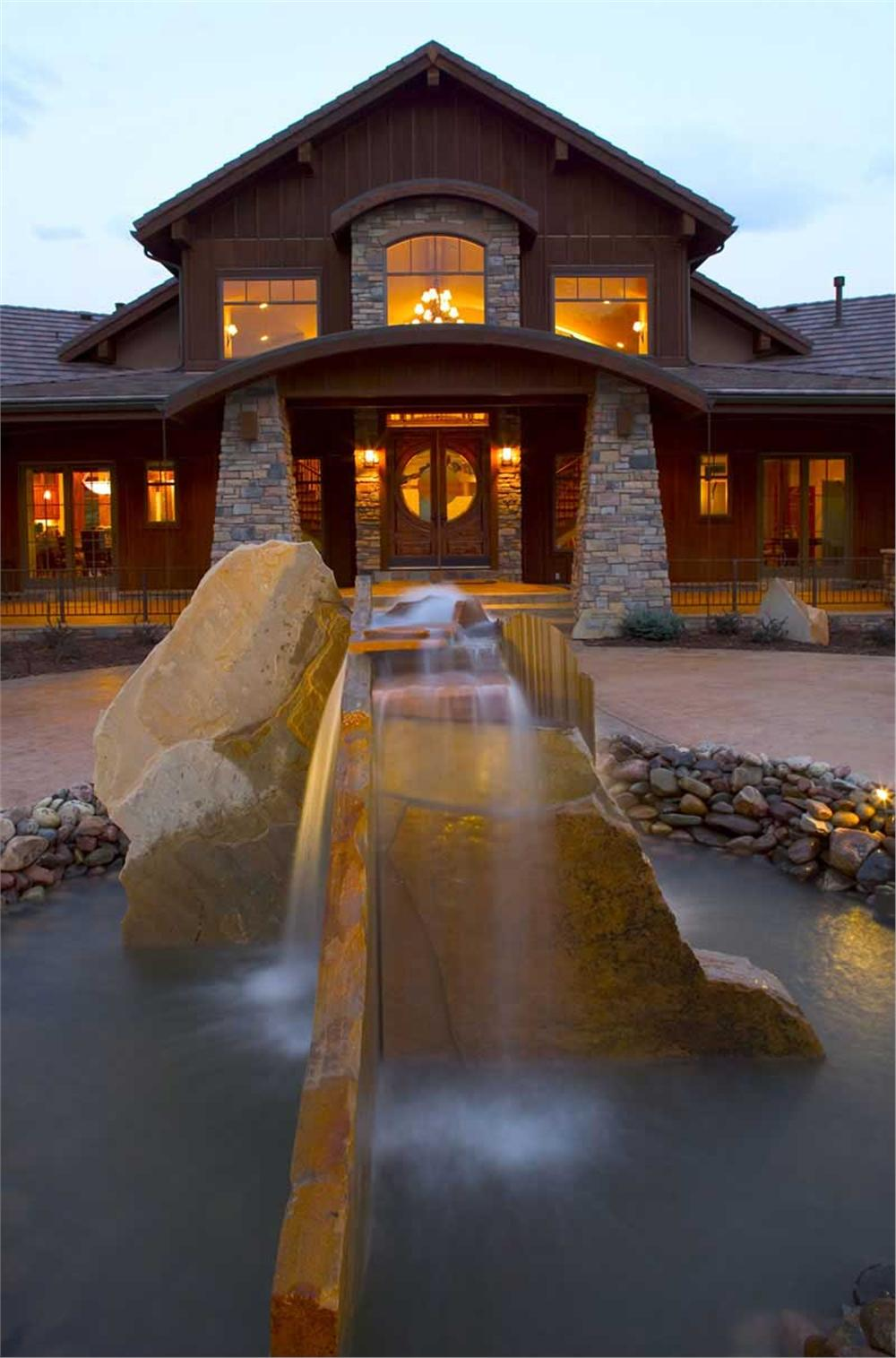Water cascades down the large rocks of the front fountain of a gorgeous 2-story, 4-bedroom Craftsman style home plan.