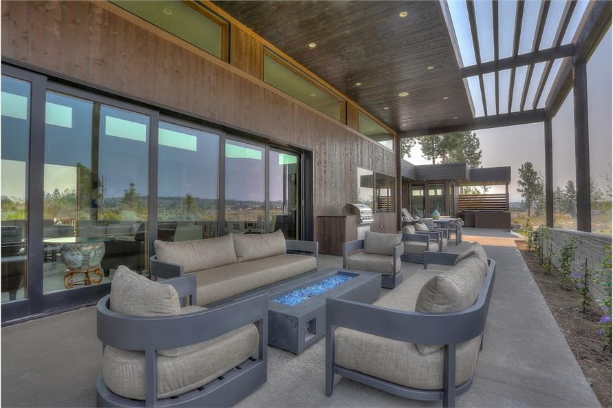 """Covered rear patio outside of a home's retractable """"wall of windows"""""""