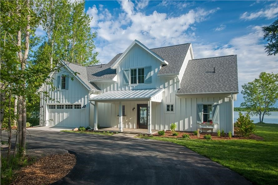 Contemporary Farmhouse style home with white vertical siding and metal porch roof