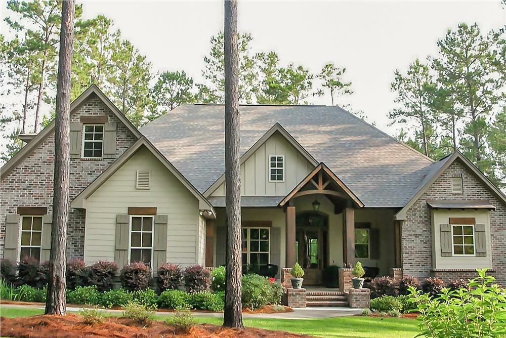 Country style home with brick and wood siding, front-forward gables on a hip roof, and covered front porch