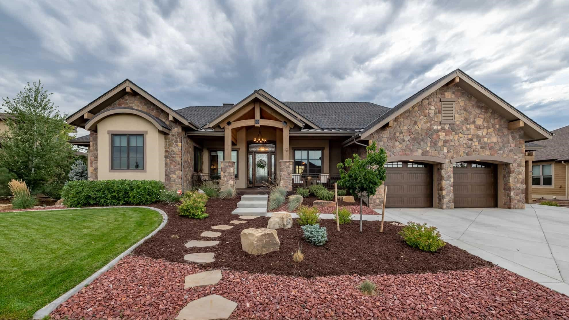 Ranch style home with stone siding, timber-frame entrance, and other rustic features