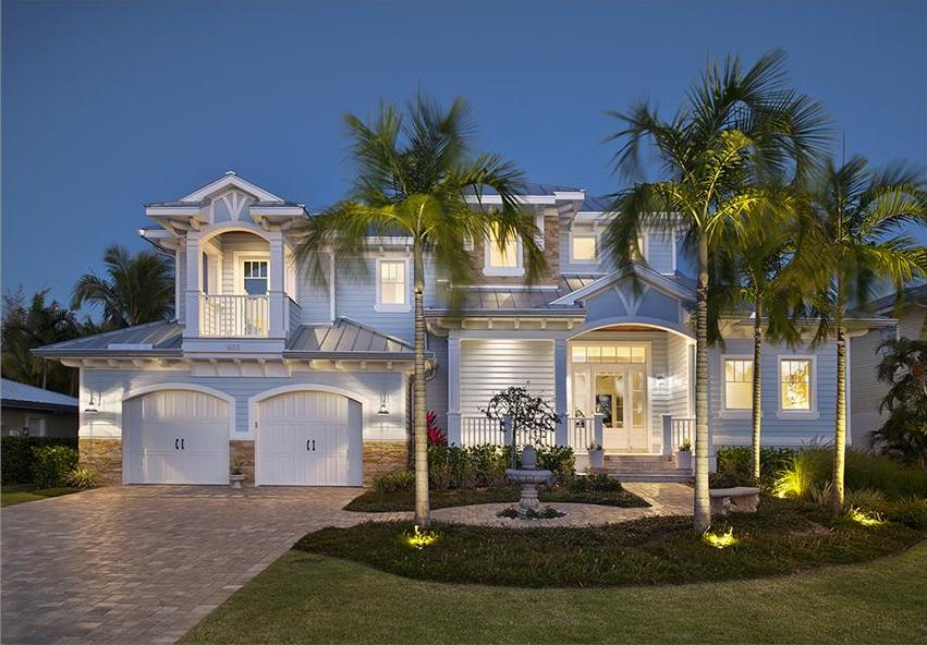 Pale blue Coastal style home with metal hip roof and stone wainscoting