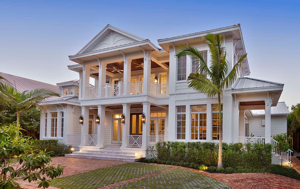Traditional Colonial style Coastal home with white siding and large windows