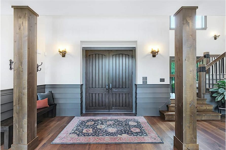 Entry foyer with white walls and wainscot treatment painted in slate blue hue