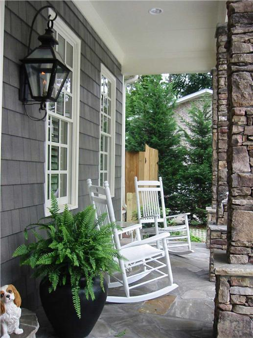 Front porch with potted fern and a pair of white rockers
