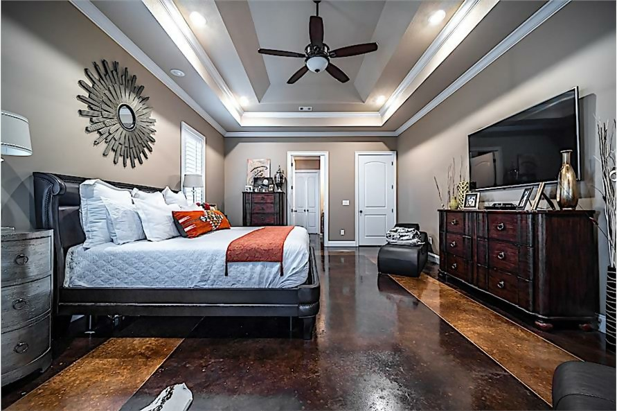 Master suite with wood floor and dark-wood, distressed furniture for a rustic feel