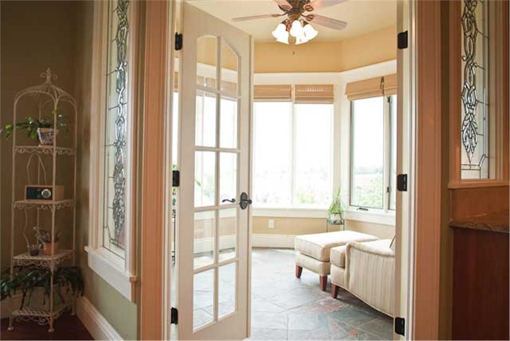 Sunroom with bumped-out window wall, neutral decor, and comfortable furniture