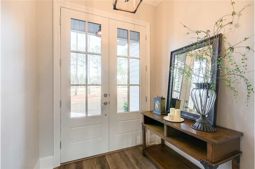 Entry foyer painted in neutral color and flooded with light from glass-panel doors