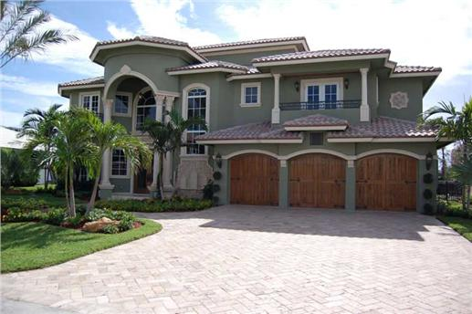 Cobblestone driveway, terra-cotta tile roof, landscaped courtyard, and tall columns of Mediterranean-style house