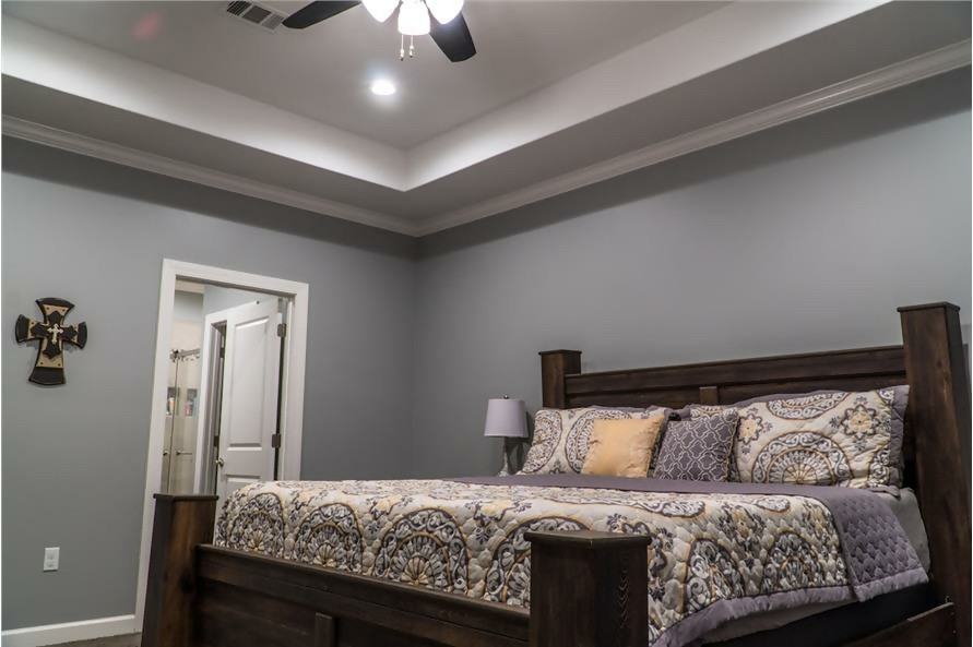 Master bedroom with tray ceiling and gray walls