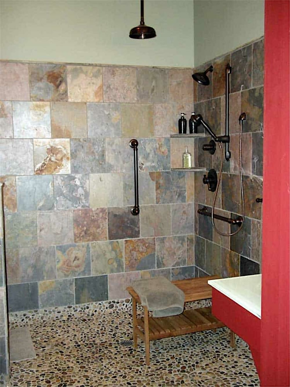 Large walk-in shower with stone-tile walls and pebble floor