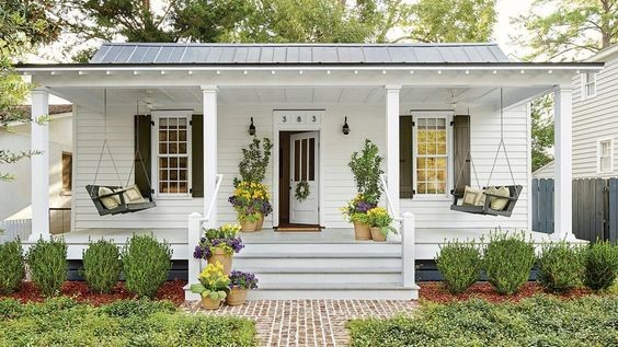 White cottage with window shutters painted dark gray to match the porch swings