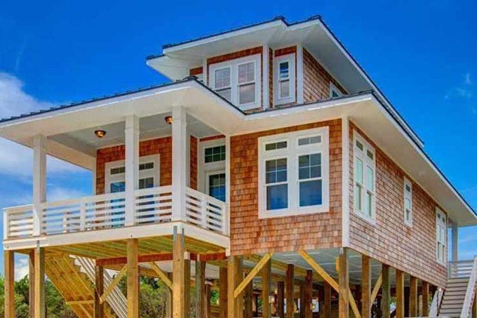 Contemporary Coastal style home built on an elevated floor foundation with a spacious porch