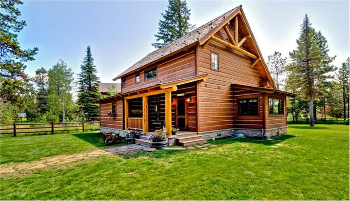 Log cabin with decorative gable treatment and covered front porch