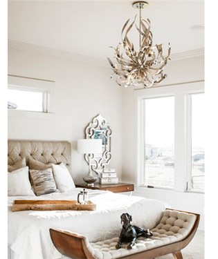 Master bedroom with gold colored chandelier crown molding that give the ceiling a bump in interest