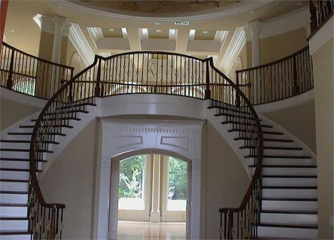 Dramatic curved double staircase with wrought-iron railing