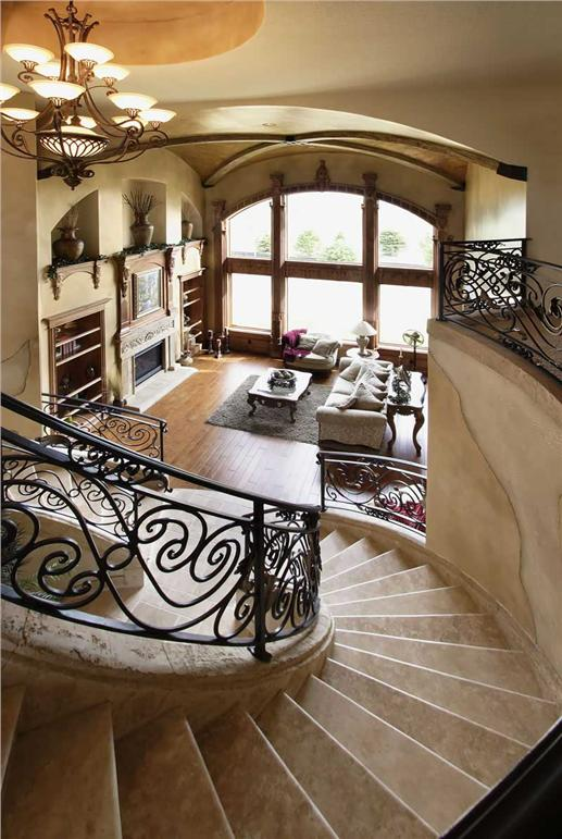 From stairs: high-ceiling Great Room with the fireplace nestled between cabinets