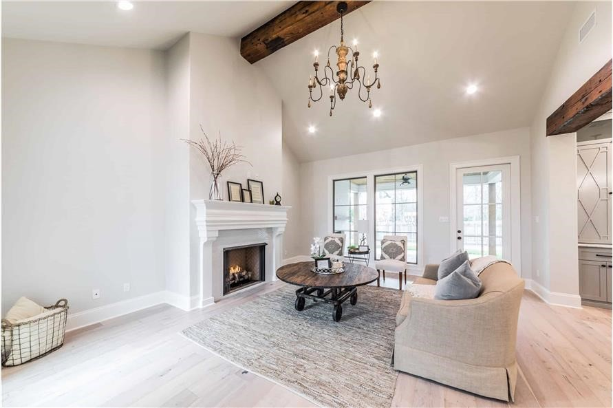 Living room decked out with neutral decor, natural wood accents, and a  fireplace in a Contemporary style home