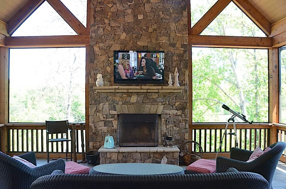 Covered rear porch with timber accents and stone fireplace