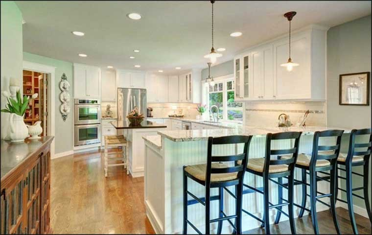 U-shape white kitchen with center island and peninsula that incorporates an eating bar