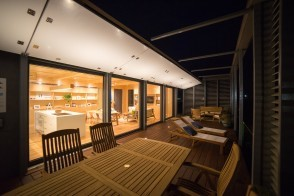 Night view of SURE House showing deck with table and chairs