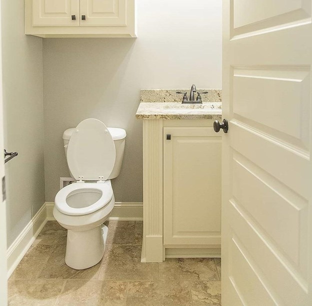White powder room with vanity, toilet, and small wall cabinet