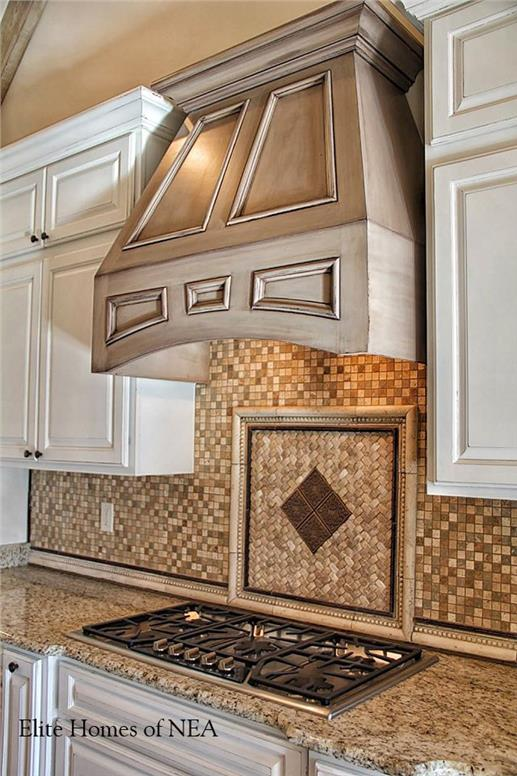 Stone and tile work behind cooktop in luxury home