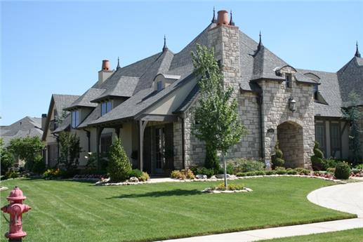 Decorative chimney, asymmetrical, steep roof lines, spires, and lush courtyard in Chateau like home