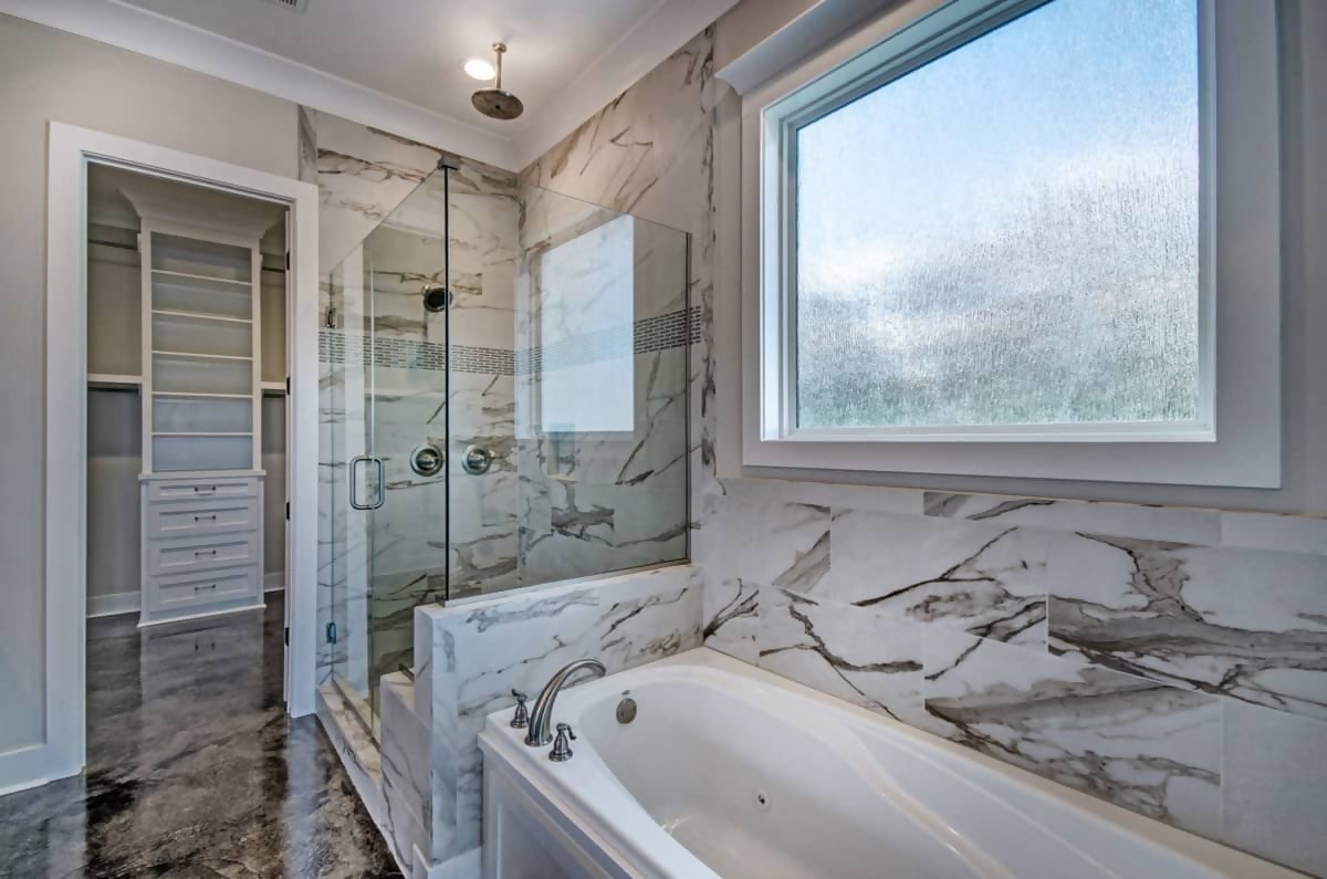 Master bathroom with glass-enclosed shower and marble-faced walls