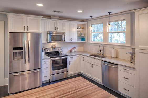 White L-shape kitchen with wood floor