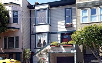 Victorian home in San Francisco bereft of embellishments and sheathed in aluminum siding