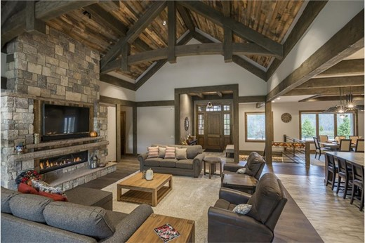 Great Rooms with exposed wooden timbers, vaulted wooden ceiling, and stone fireplace