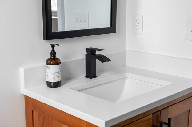 Bathroom vanity with dark faucet and mirror above