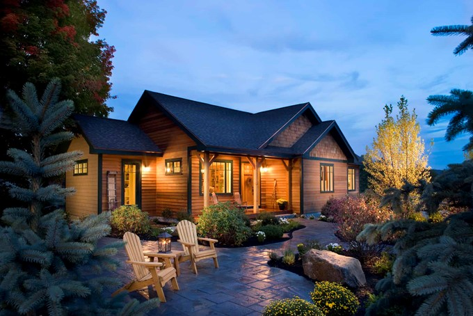One-story country cabin with wood siding, covered front porch, and timber porch columns